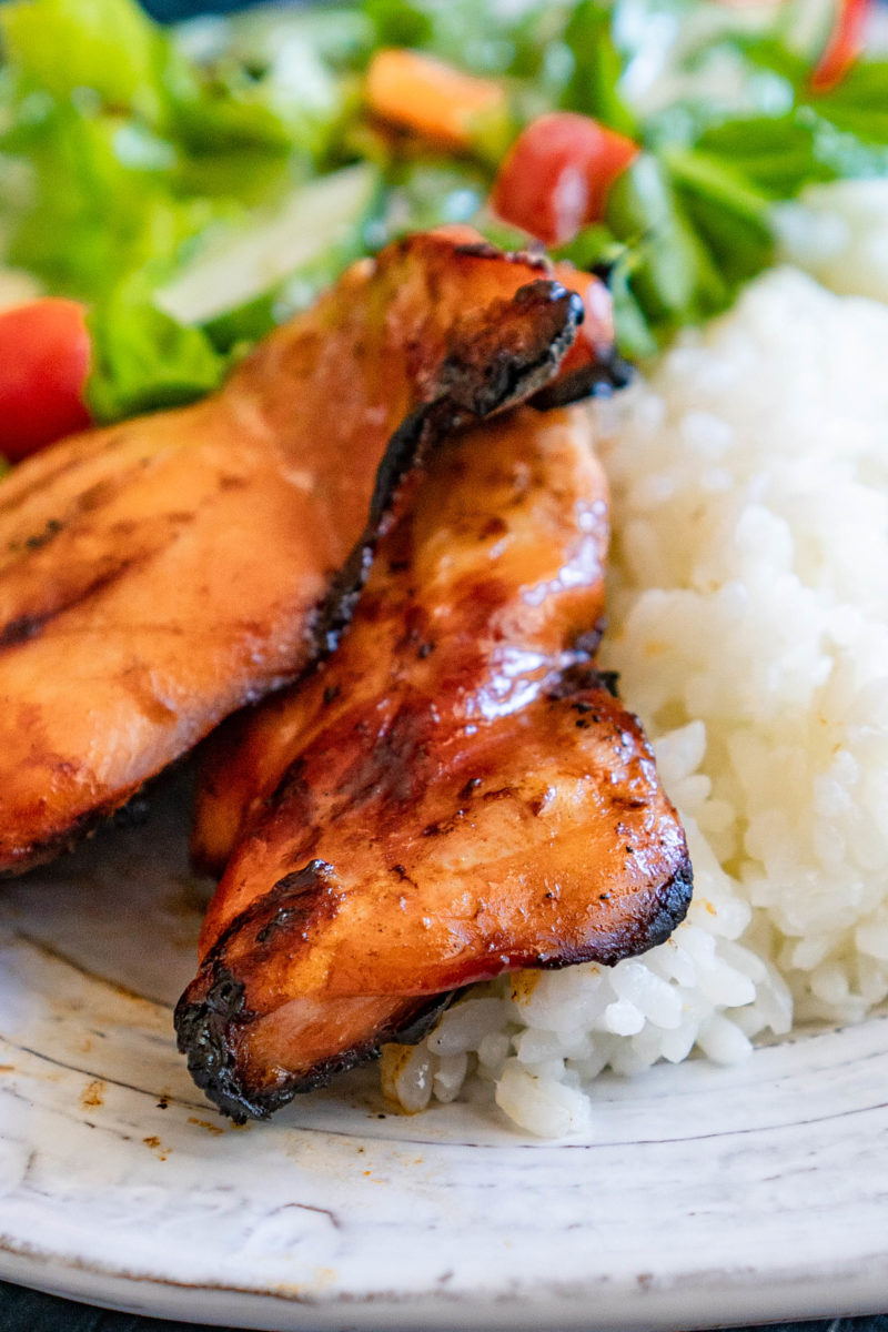 Grilled Teriyaki Chicken thighs next to rice and salad on a white plate