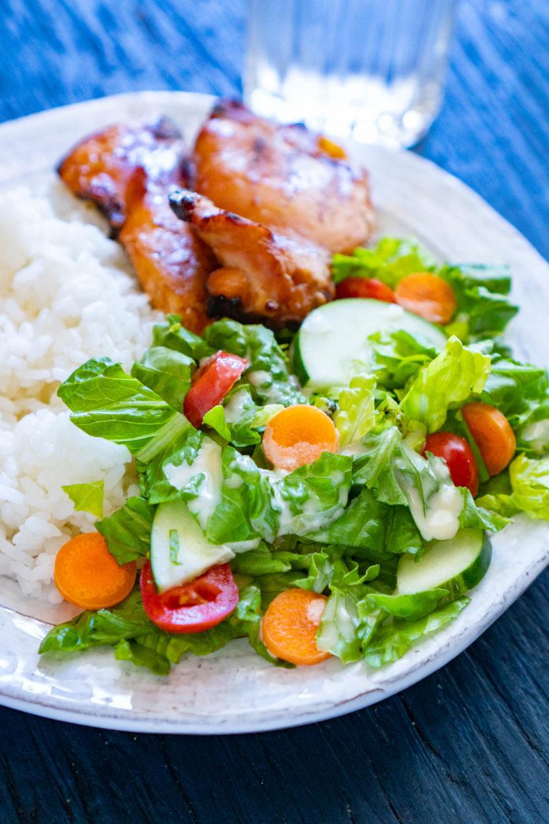 Teriyaki plate with chicken, rice, and salad topped with teriyaki salad dressing