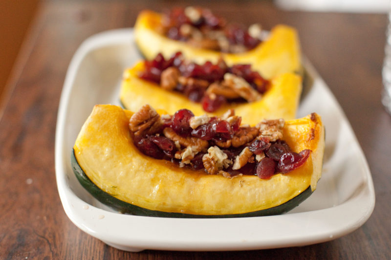 Vegetarian recipe for stuffed acorn squash that tastes like fall. Roasted acorn squash stuffed with crunchy pecans, tangy cranberries, & sweet brown sugar. From EatingRichly.com