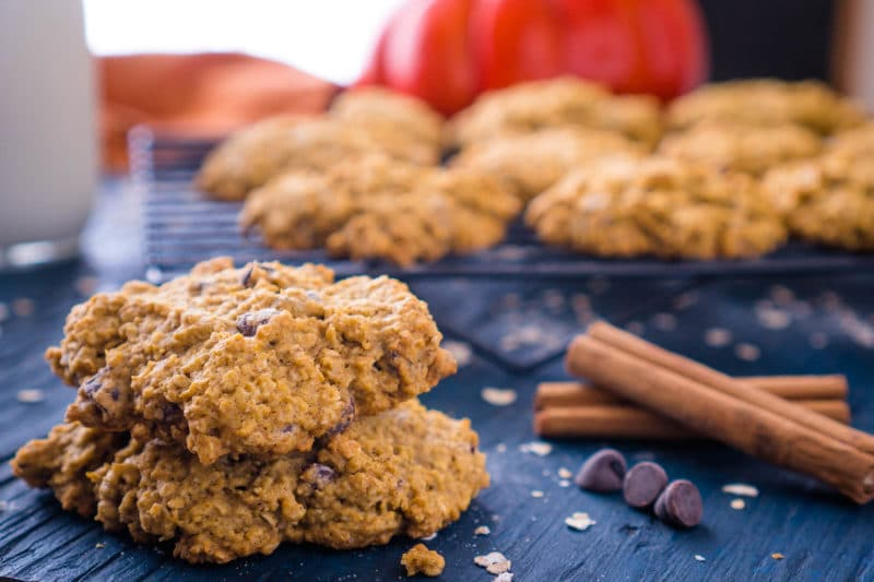 Pumpkin oatmeal chocolate chip cookies stacked next to more cookies on a cooling rack