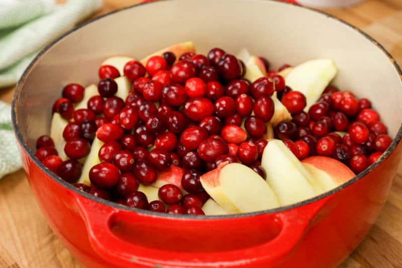 sliced Apples and fresh cranberries in a red Dutch oven