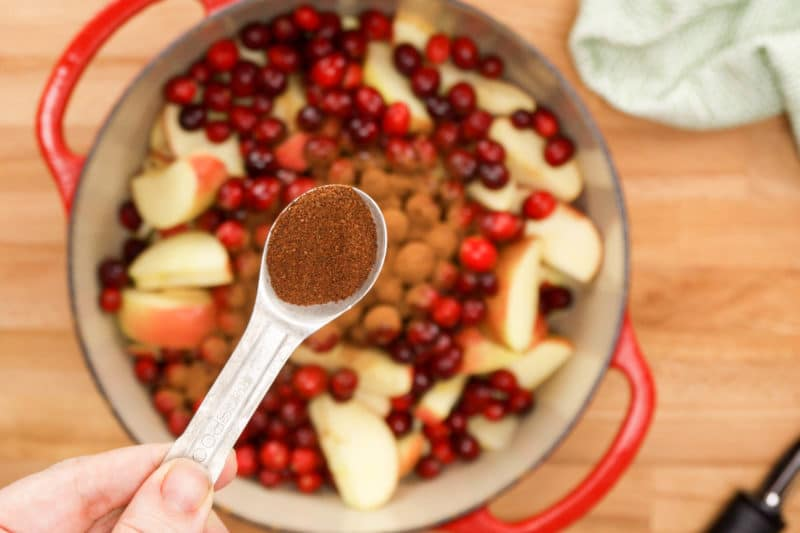 A teaspoon of cloves held over a pot of cranberries and apples