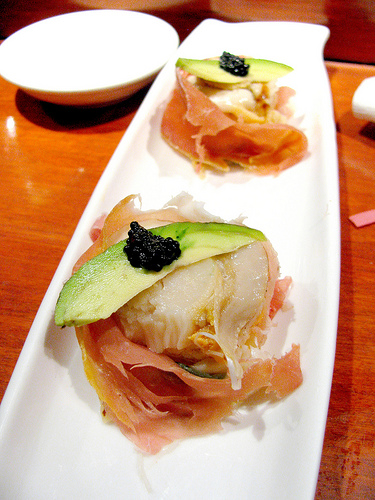 Seventh course: whole scallops wrapped in prosciutto topped with avocado and caviar