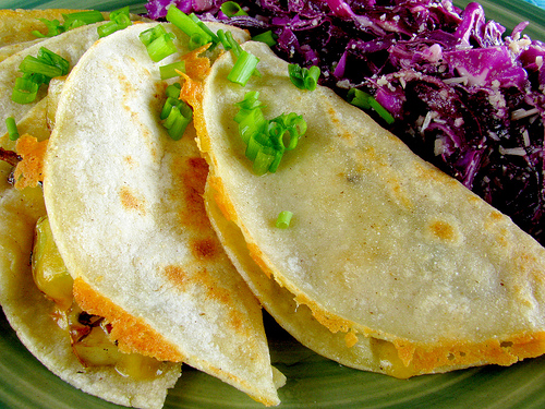 Potato Cheese Quesadillas garnished with chopped green onions.