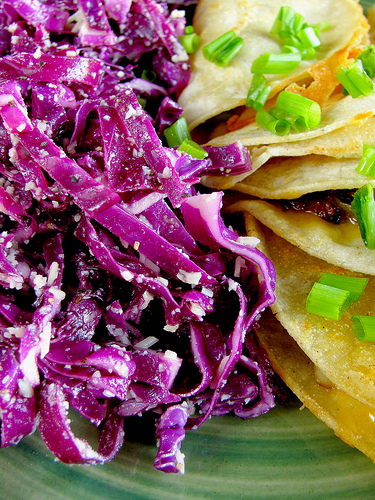 Closeup of parmesan red cabbage salad and potato cheese tacos.