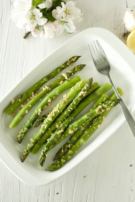 shallow white dish with lemon garlic asparagus