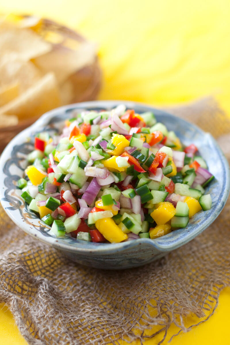 Grey blue hand thrown bowl of colorful fresh salsa with chunks of mango, red bell pepper, cucumber, red onion, and jalapeno