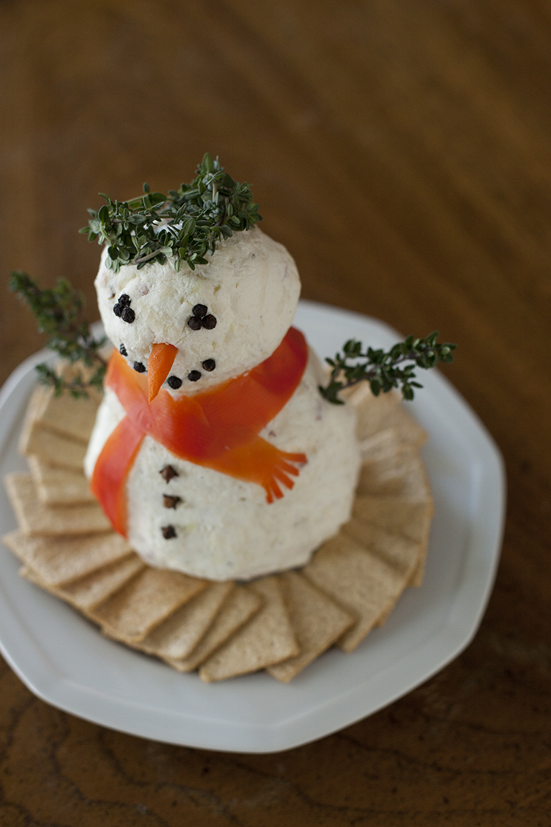 This cute Christmas cheeseball snowman is the perfect appetizer recipe for your holiday party. Fast & easy to make, & can double as an edible centerpiece! From EatingRichly.com