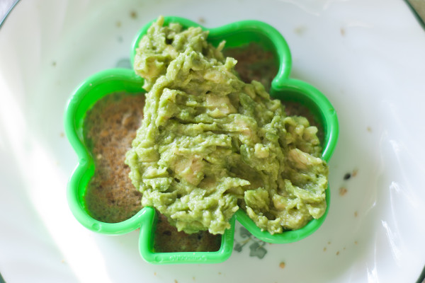 A healthy St. Patrick's Day breakfast with whole grain avocado shamrock toast and egg in a basket - EatingRichly.com