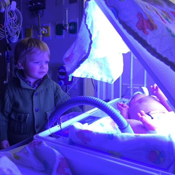 big brother watching over baby in hospital