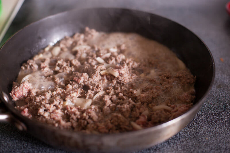 Cooking ground beef and onions in a skillet