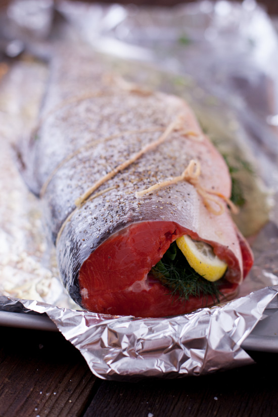 Learn how to cook whole salmon in the oven, the easy way! This healthy recipe for whole salmon stuffed with lemon & herbs makes salmon an affordable option. From EatingRichly.com
