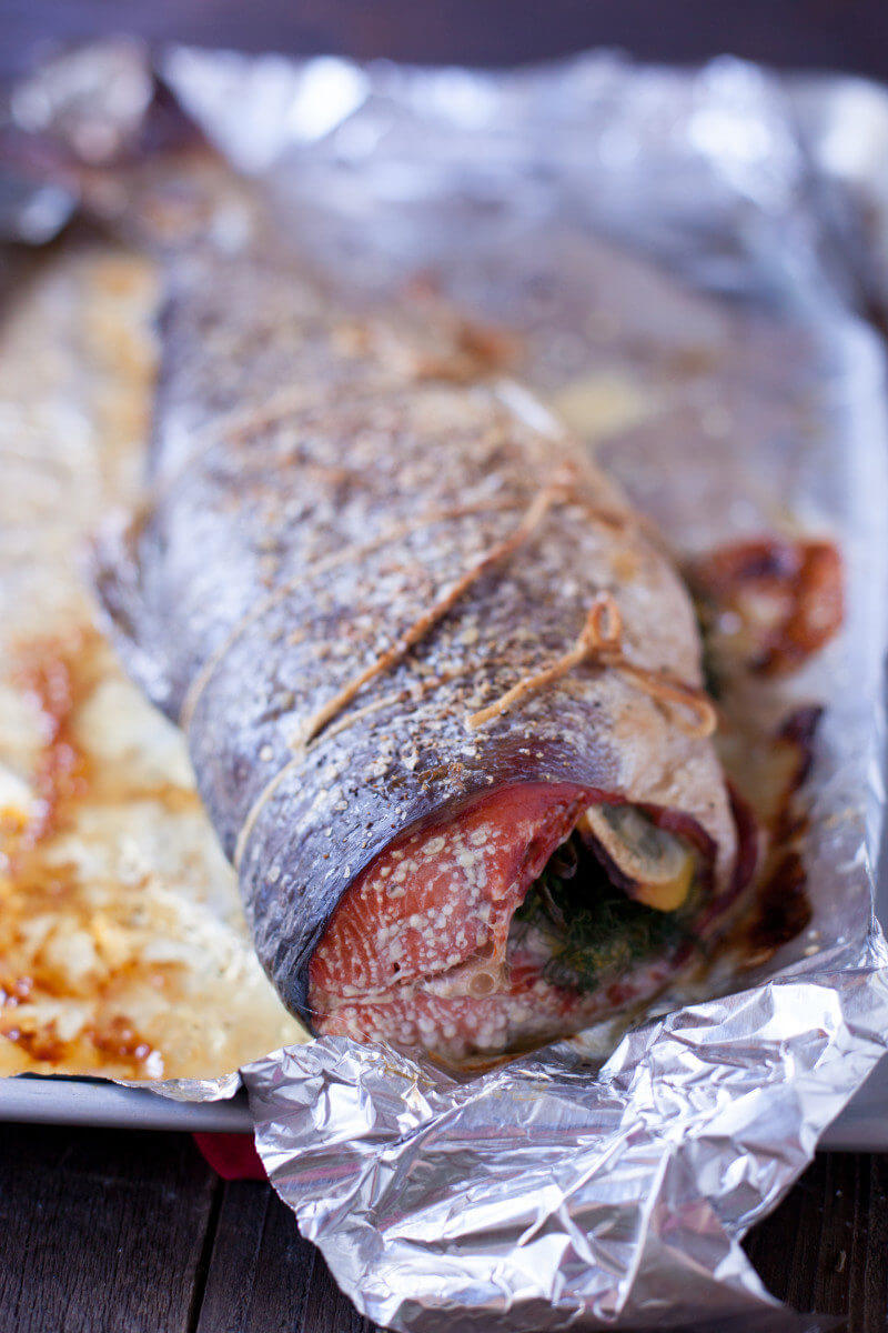 baked whole salmon stuffed with lemon slices and herbs