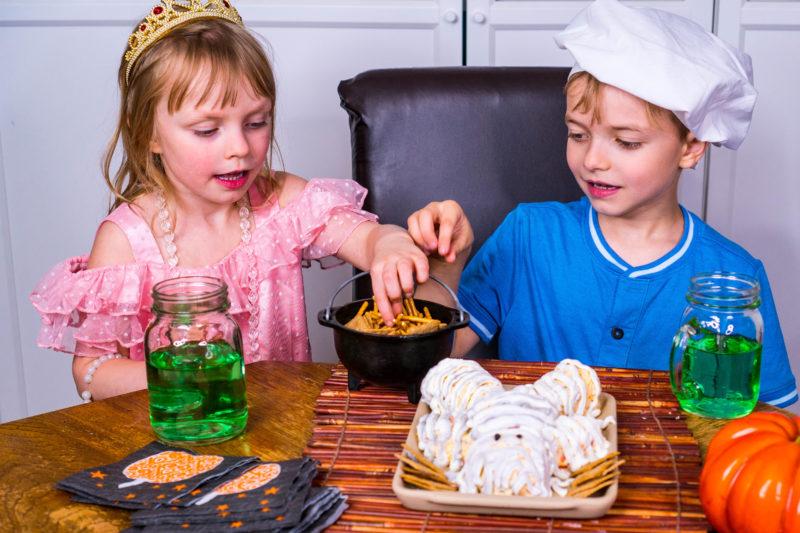 Kids in costume eating Halloween cheese ball mummy