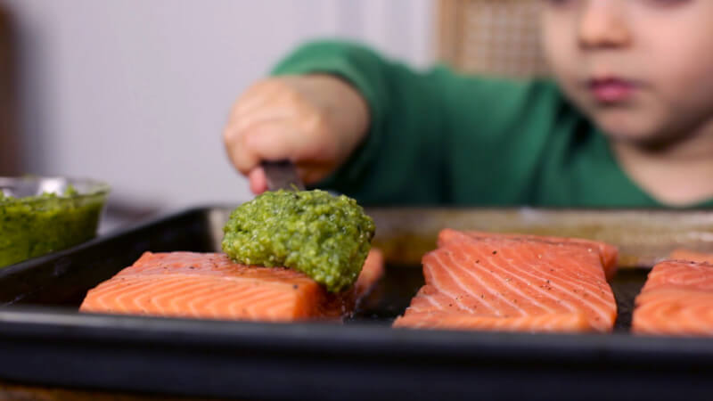 This easy salmon recipe is simple enough for a toddler to make! Kids love the colorful pesto & crunchy pistachios, making it a perfect way to introduce fish to your little ones. Part of #MiniChefMondays on EatingRichly.com