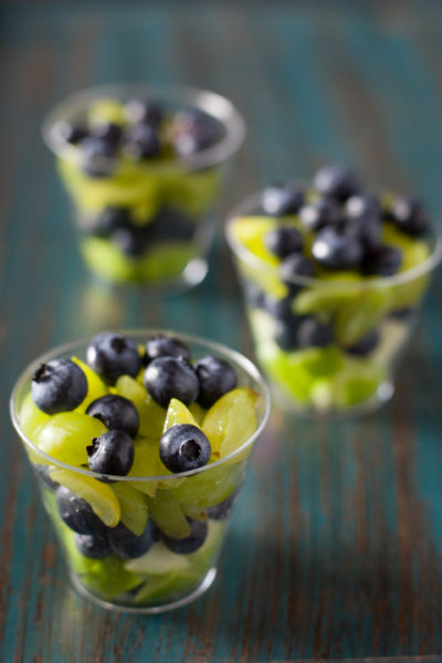 This fruit salad is a healthy football appetizer that's perfect for Seahawks fans. Green apples and grapes are layered with blueberries in individual servings for a football snack that is so easy to make, a toddler can do it! Part of #MiniChefMondays on EatingRichly.com