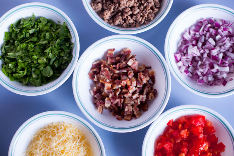 Guacamole bacon burger dip has all the flavors of your favorite burger, turned into a seven layer dip. It's the perfect football snack recipe! Easy to make the day before as well. From EatingRichly.com