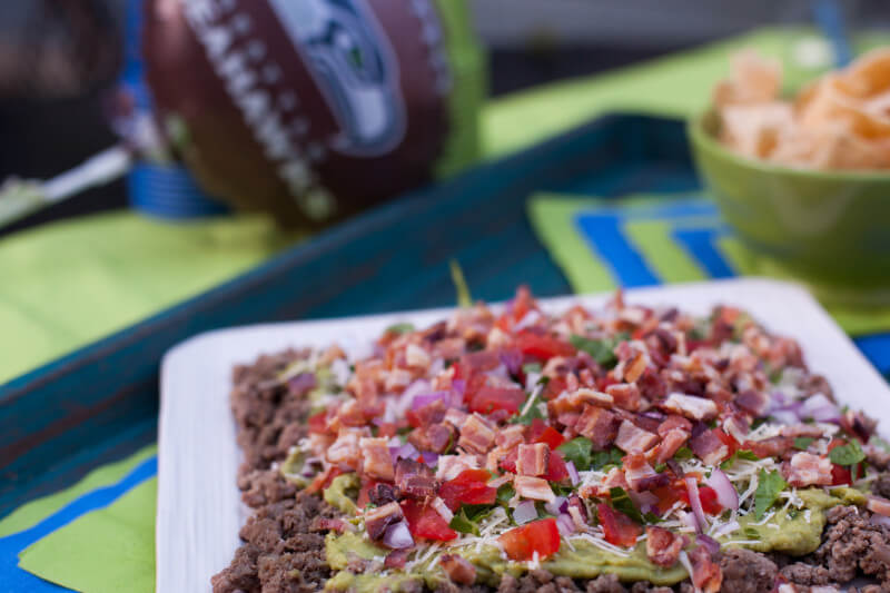 Cute Seahawks fan. guacamole bacon burger dip has all the flavors of your favorite burger, turned into a seven layer dip. It's the perfect football snack recipe! Easy to make the day before as well. From EatingRichly.com