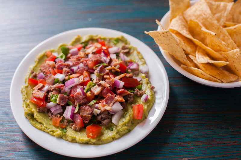 Dairy free Guacamole bacon burger dip has all the flavors of your favorite burger, turned into a seven layer dip. It's the perfect football snack recipe! Easy to make the day before as well. From EatingRichly.com
