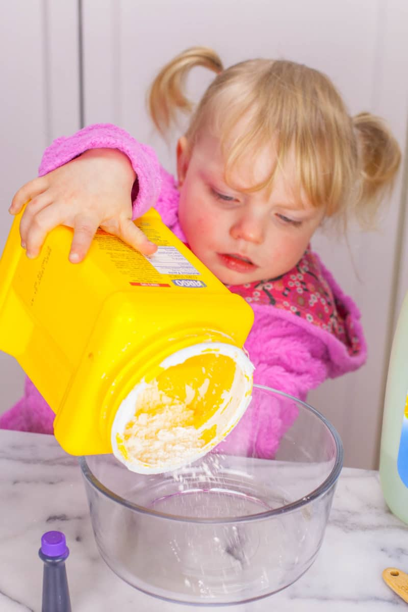 Little girl dumping cornstarch into a bowl