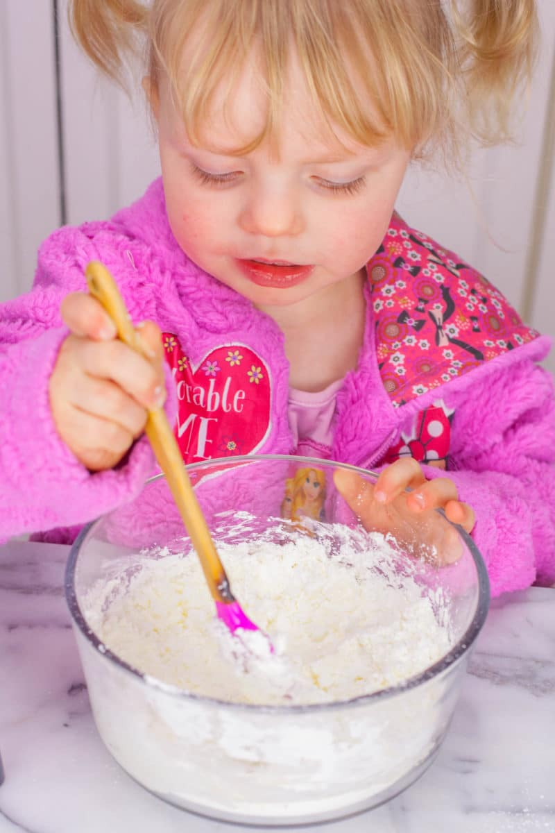 Little girl mixing cornstarch and dish soap for silly putty