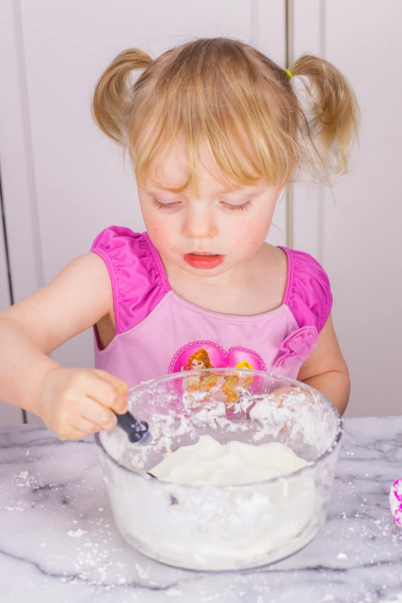 Girl adding food dye to homemade silly putty