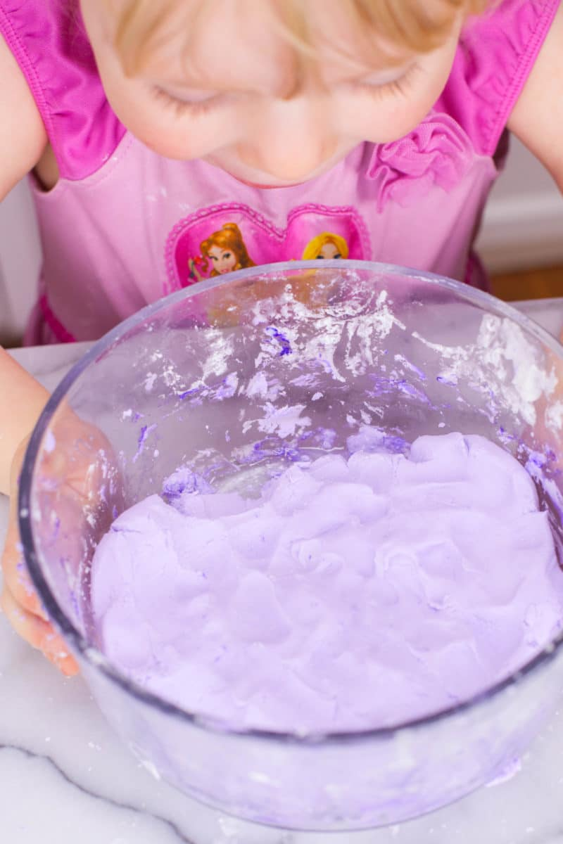 Girl looking at purple homemade silly putty in a bowl