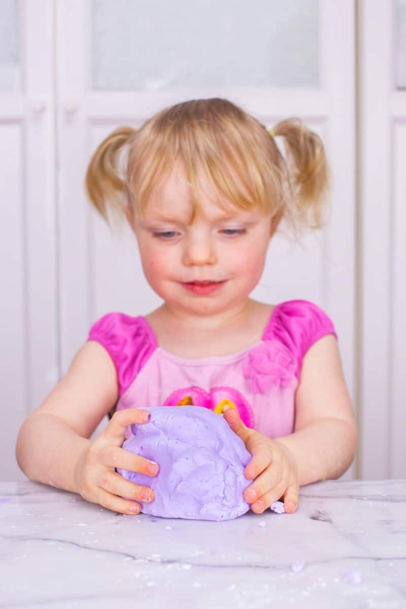 Little Girl playing with purple homemade silly putty