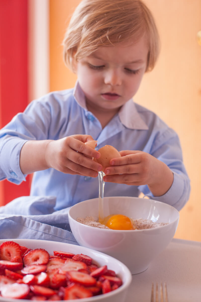 Three year old kid chef getting ready to bake an easy strawberry cobbler for dessert. From EatingRichly.com