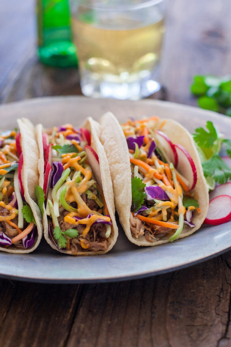 Korean tacos filled with easy flavorful crockpot pulled pork, crunchy veggies, and sweet and spicy sauces. You could start your own food truck with these! From EatingRichly.com