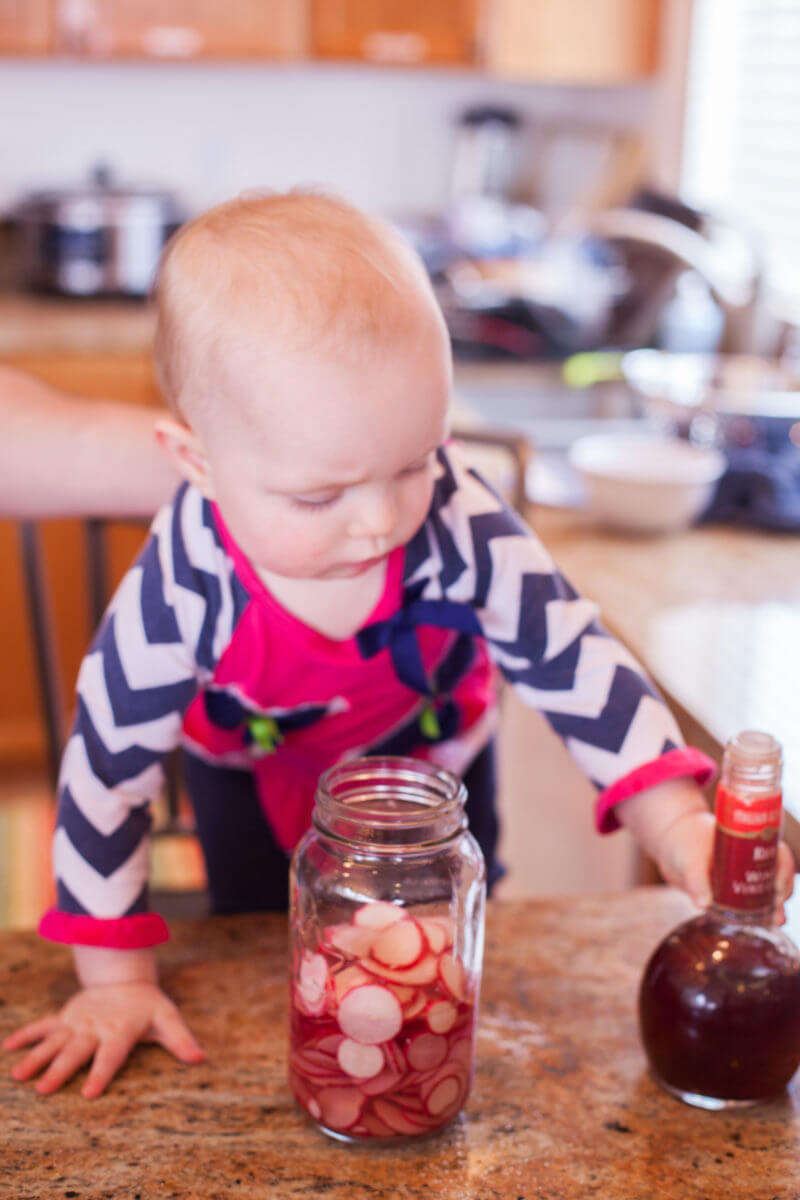 Baby making quick pickled radishes for Korean tacos. Get the recipes at EatingRichly.com