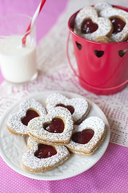 heart shaped sandwich cookies on a lace and pink table