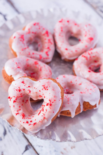 These strawberry sprinkle donut hearts are made with crumbled freeze dried strawberries, and a sweet lemon glaze, for a gorgeous dye free strawberry lemonade treat perfect for Valentine's Day. From EatingRichly.com