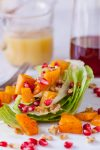 This gorgeous fall wedge salad with romaine is topped with cinnamon roasted butternut squash, pomegranate seeds, and a creamy citrus honey mustard dressing. From EatingRichly.com