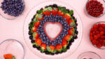Blackberries Strawberries and blueberries around a heart cookie cutter
