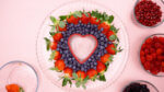 Strawberries and blueberries around a heart cookie cutter