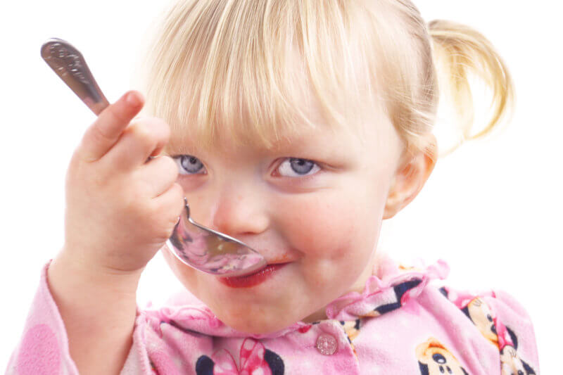 Toddler taking a spoonful of elderberry syrup