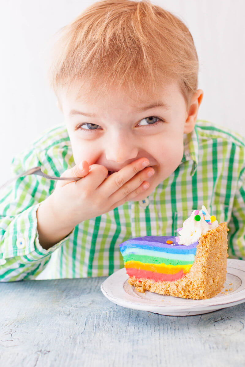 Child laughing with rainbow cheesecake