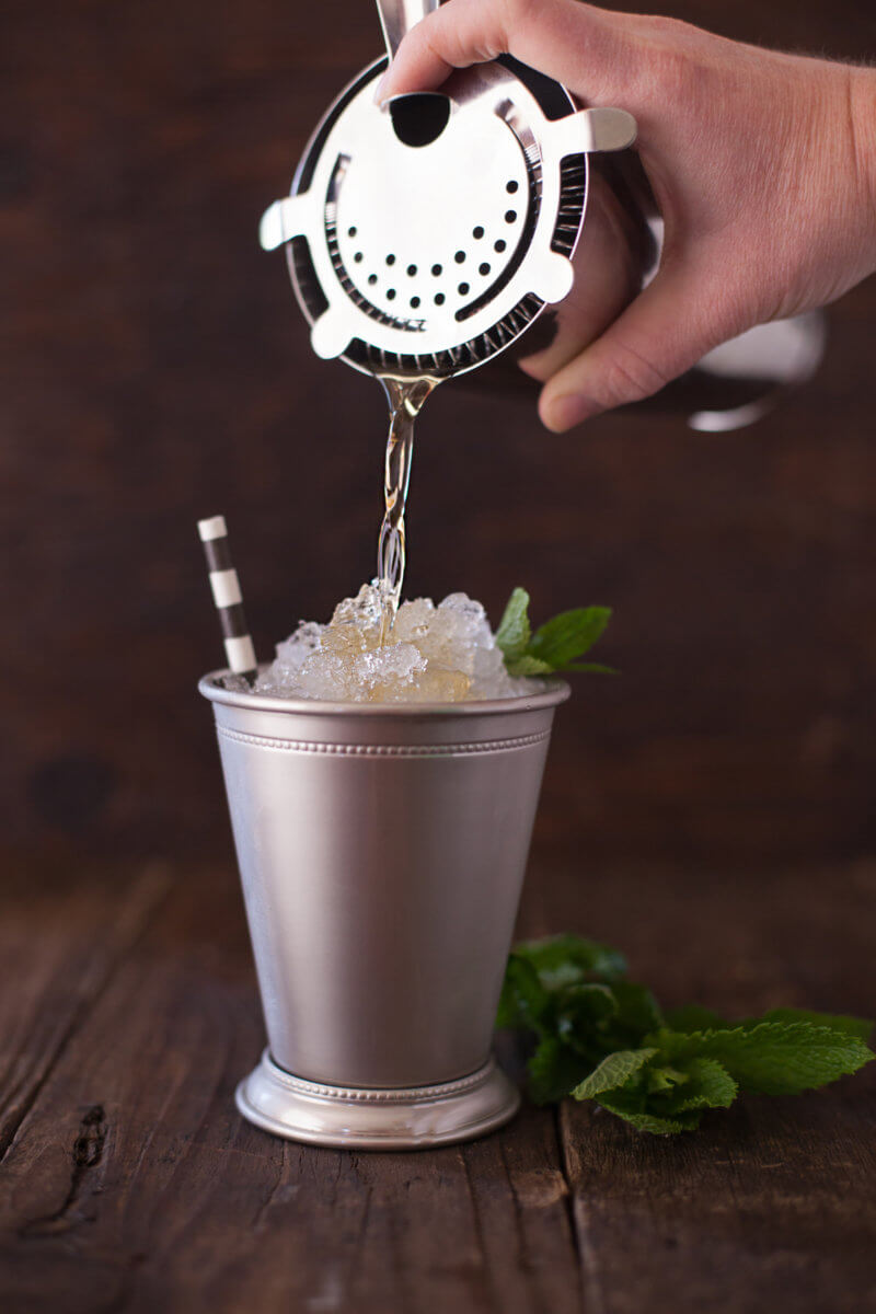 Pouring a mint julep from a cocktail shaker