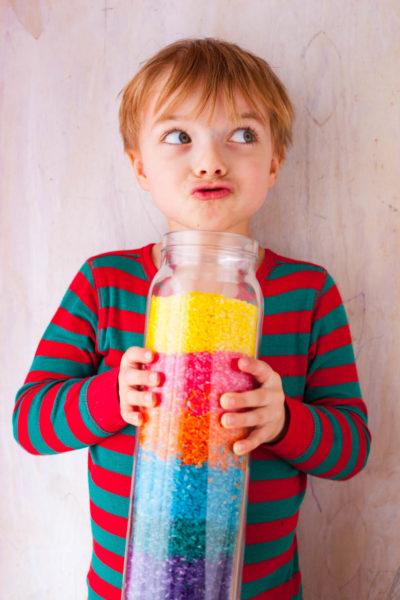 Boy holding jar of rainbow rice