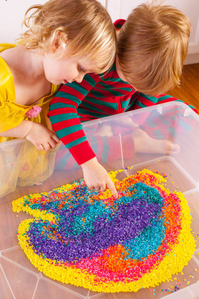 Kids playing in rainbow rice sensory bin