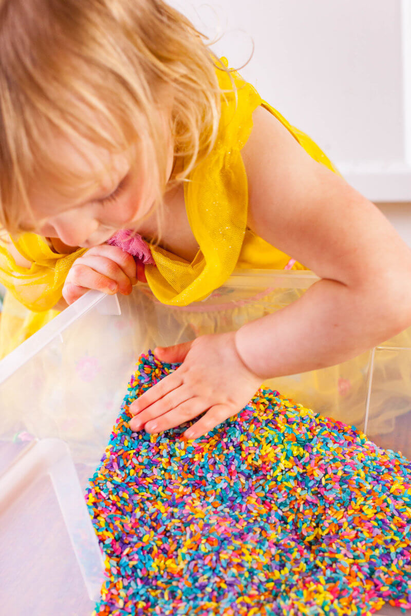Toddler playing with rainbow rice sensory bin