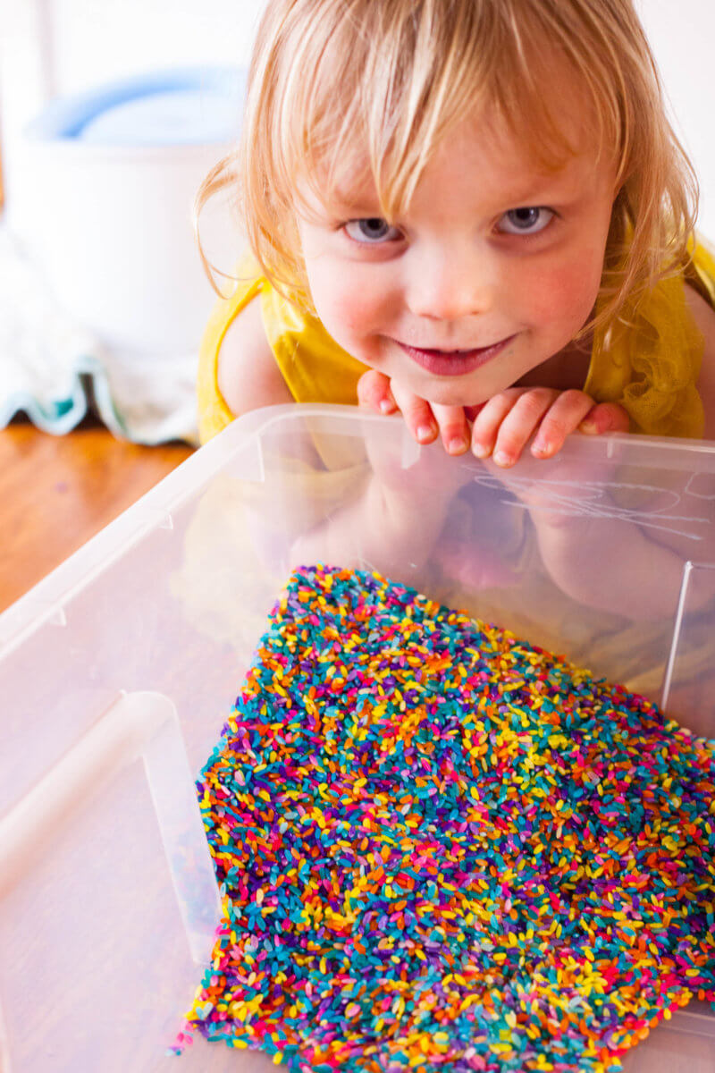 toddler with rainbow rice sensory bin