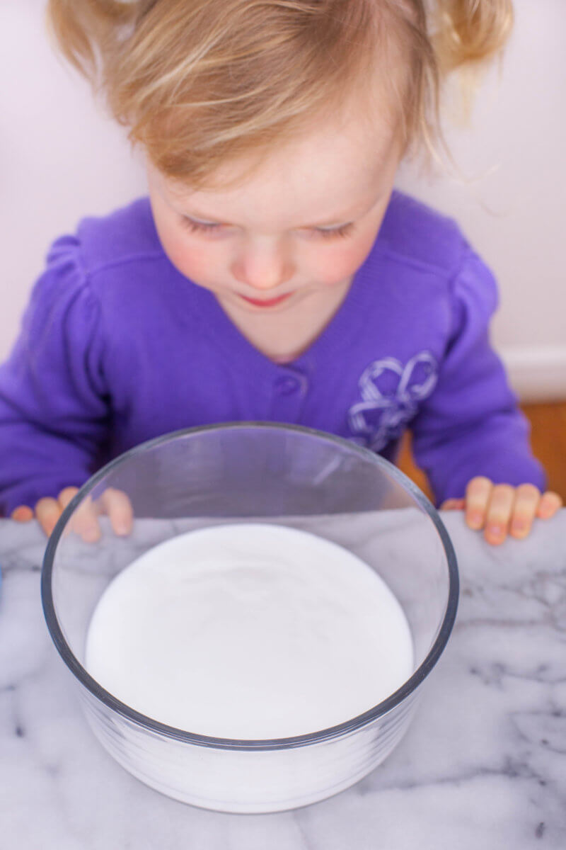 toddler with glue in a bowl for fluffy slime