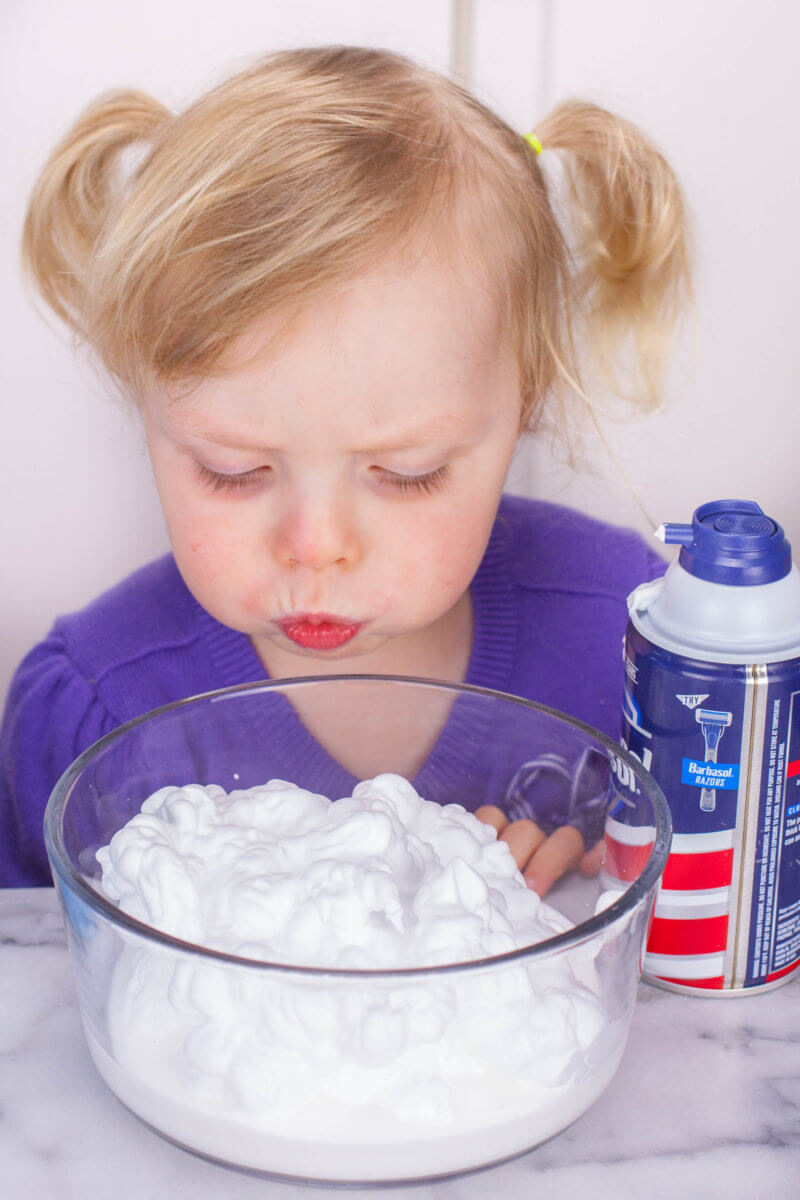 toddler blowing on shaving cream in a bowl