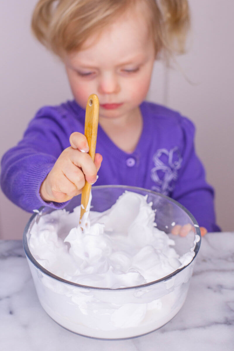 toddler mixing fluffy slime ingredients