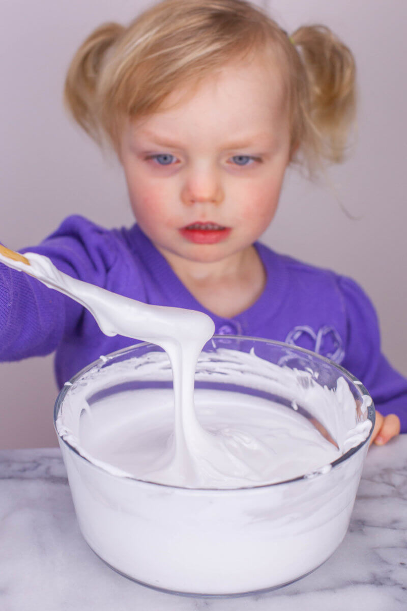 toddler stirring fluffy slime base