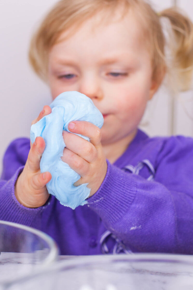 toddler kneading fluffy slime