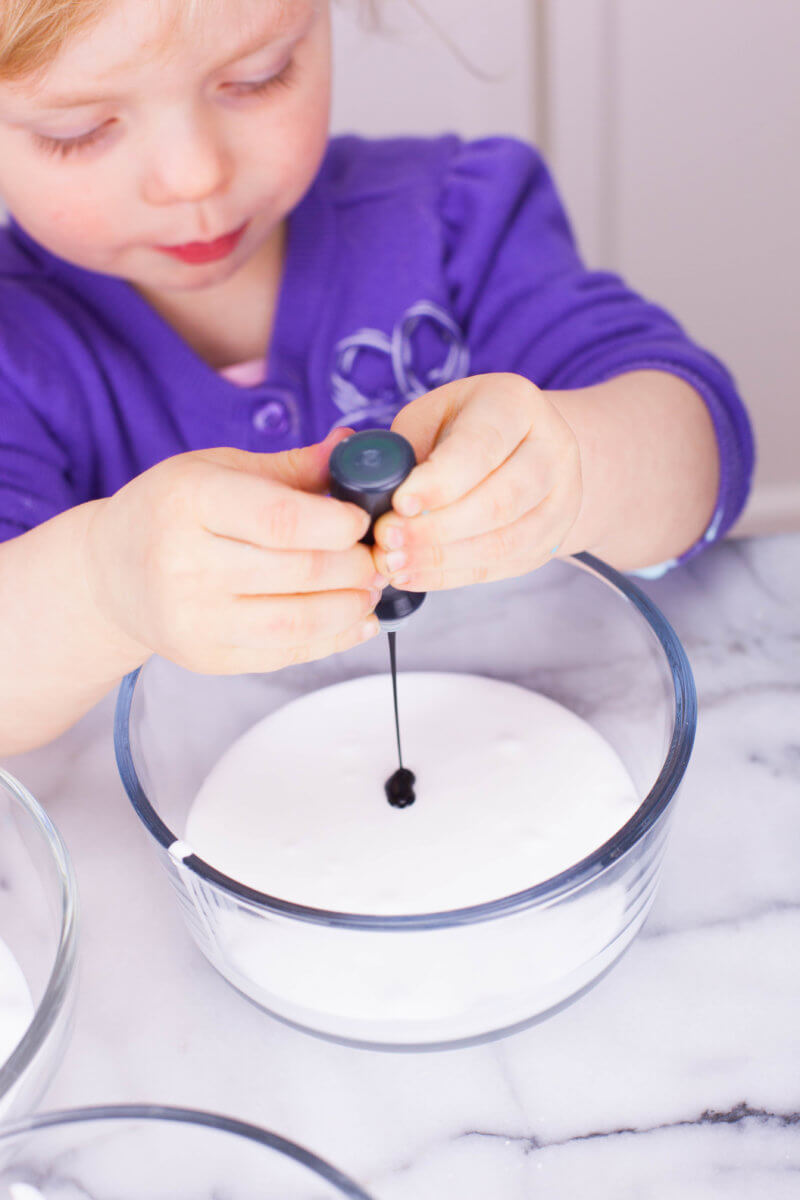 toddler adding food coloring to slime