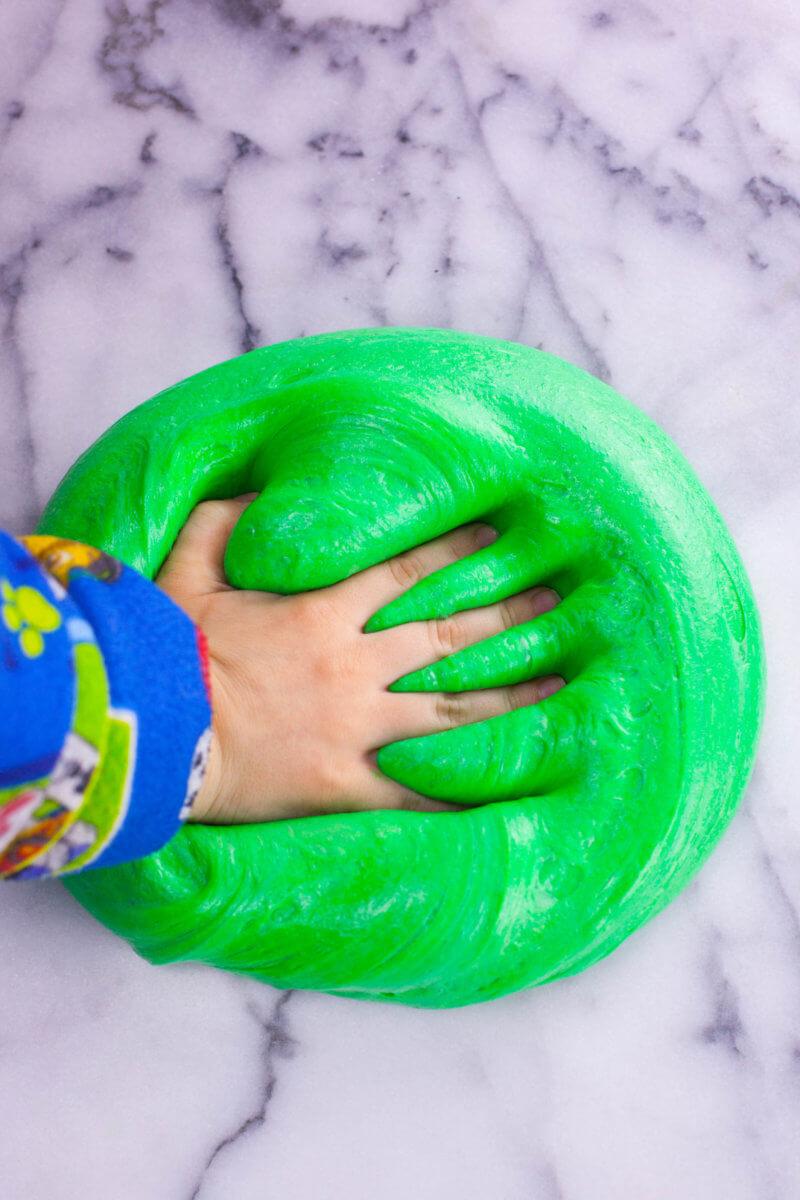hand squishing fluffy slime